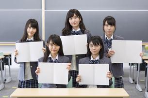 教室でノート開いて微笑む女子高校生たちのポートレートの写真素材 [FYI02971633]