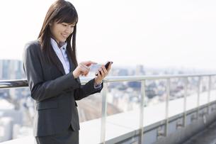 屋上でスマートフォンにタッチするビジネス女性の写真素材 [FYI02971638]