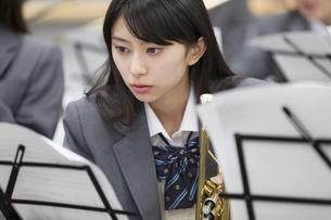 音楽室で楽譜をみる女子学生の写真素材 [FYI02971639]