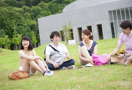 芝に座り談笑する学生たちの写真素材 [FYI02971642]