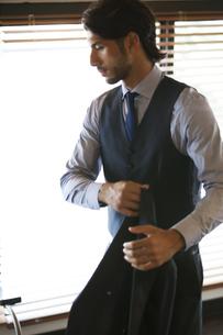 オフィスでスーツのジャケットを片手に持つビジネス男性の横顔の写真素材 [FYI02971644]