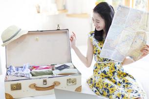 旅行の準備をする笑顔の女性の写真素材 [FYI02971649]