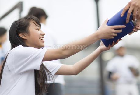 ドリンクボトルを手渡す女子マネージャーの写真素材 [FYI02971650]