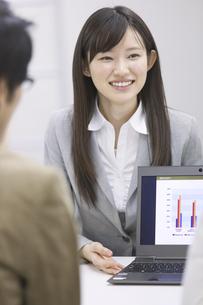 パソコンを使って接客するビジネス女性の写真素材 [FYI02971655]