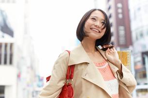 買い物中に街で微笑む女性の写真素材 [FYI02971656]