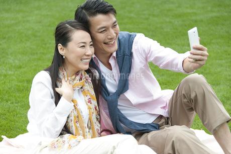 芝に腰かけてスマートフォンを見るカップルの写真素材 [FYI02971657]