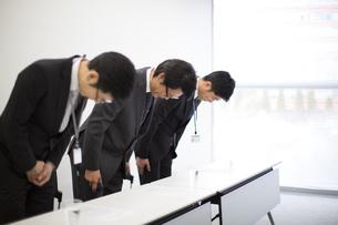 謝罪会見で頭を下げるビジネス男性3人の写真素材 [FYI02971658]