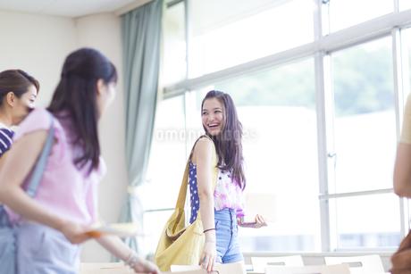 教室で机に向いながら笑い合う学生たちの写真素材 [FYI02971661]