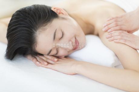 うつ伏せで肩をマッサージされている女性の写真素材 [FYI02971664]