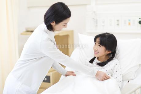 女の子に布団をかける女性看護師の写真素材 [FYI02971666]