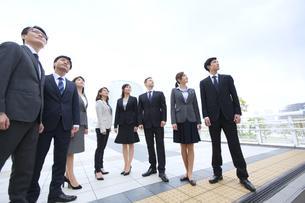 オフィスビルを背景に上を見上げて立つビジネス男女の写真素材 [FYI02971674]