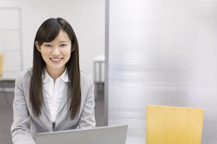 ノートパソコンの前で微笑むビジネス女性の写真素材 [FYI02971676]