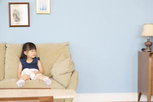 ソファーに座って遠くを眺める女の子の写真素材 [FYI02971677]