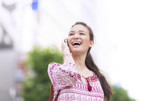 スマートフォンで話す若い女性の写真素材 [FYI02971694]