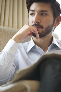 ソファーに座って考え込む男性の写真素材 [FYI02971699]