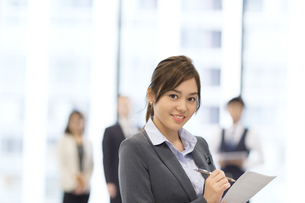 オフィスビルのロビーで資料を持って微笑むビジネス女性の写真素材 [FYI02971700]