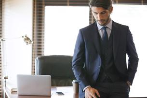 オフィスのデスクに寄りかかるビジネス男性の写真素材 [FYI02971701]