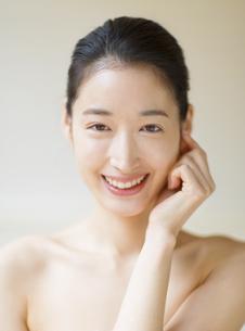 頬に片手を添えて微笑む女性の写真素材 [FYI02971704]