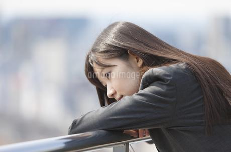 柵に肘をかけてうつむくビジネス女性の写真素材 [FYI02971705]
