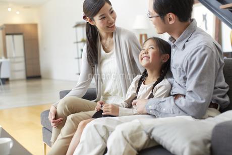 ソファーで会話する3人家族の写真素材 [FYI02971706]