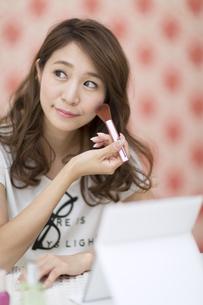 鏡の前でメイクアップをする女性の写真素材 [FYI02971708]