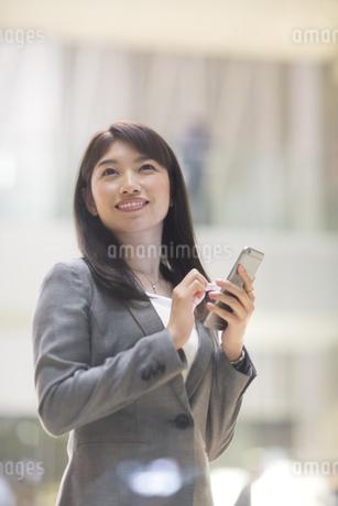 スマートフォンを持ち上を見上げて微笑むビジネス女性の写真素材 [FYI02971712]