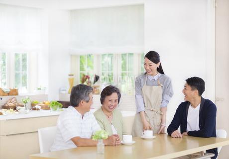 ダイニングテーブルで談笑する家族の写真素材 [FYI02971717]