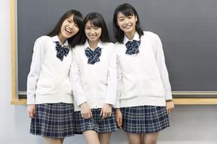 黒板の前に笑顔で並ぶ女子高校生たちのポートレートの写真素材 [FYI02971722]