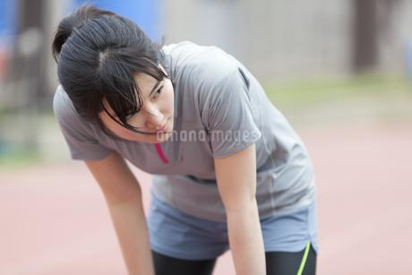 陸上競技場で休憩している女子学生の写真素材 [FYI02971725]
