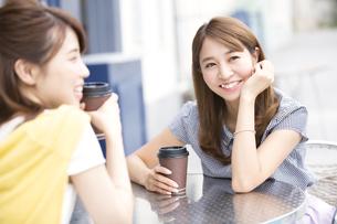 街中でカップを持って会話を楽しむ2人の女性の写真素材 [FYI02971727]