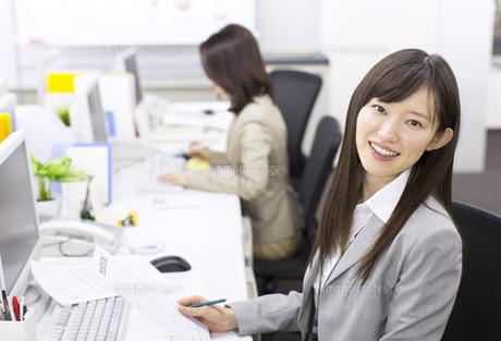 デスクで資料を手に微笑むビジネス女性の写真素材 [FYI02971730]