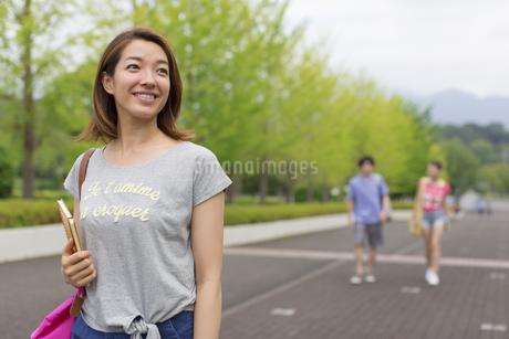微笑みながらキャンパスを歩く女子学生の写真素材 [FYI02971734]