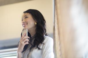 スマートフォンを持って微笑むビジネス女性の写真素材 [FYI02971735]
