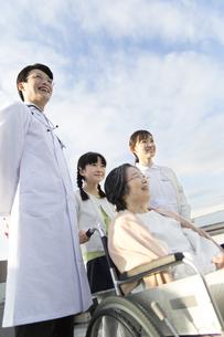 屋上で車椅子の患者に添う医師と看護師と女の子の写真素材 [FYI02971738]