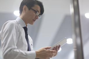 タブレットPCを見るビジネス男性の横顔の写真素材 [FYI02971750]