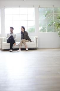 ソファーに座って微笑む男性と女性の写真素材 [FYI02971756]