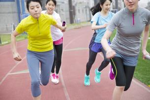陸上競技場でバトンの手渡しをする女子学生たちの写真素材 [FYI02971758]