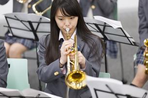 音楽室でトランペットを演奏する女子学生の写真素材 [FYI02971771]