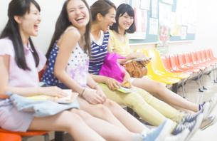 廊下の椅子に並んで座って笑い合う女子学生たちの写真素材 [FYI02971777]