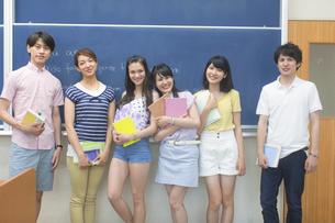 黒板の前に笑顔で並ぶ学生たちのポートレートの写真素材 [FYI02971780]