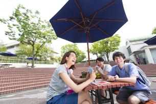 キャンパスの野外のテーブルに座って笑う3人の学生の写真素材 [FYI02971781]