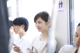 電車の座席に座り遠くを見つめるビジネス女性の写真素材 [FYI02971784]