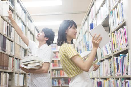 図書室で棚から本を引き出す男女の学生の写真素材 [FYI02971785]