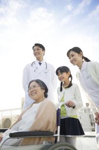 屋上で車椅子の患者に添う医師と看護師と女の子の写真素材 [FYI02971786]