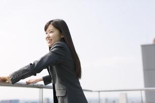 屋上で遠くを見ながら微笑むビジネス女性の写真素材 [FYI02971789]