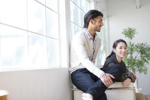 ソファーに座って微笑む男性と女性の写真素材 [FYI02971792]