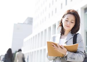 立ち止まって手帳にメモをするビジネス女性の写真素材 [FYI02971793]