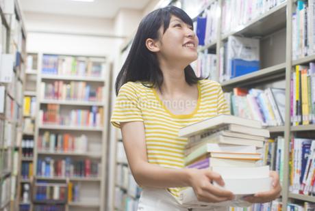 図書室で重ねた本を運ぶ女子学生の写真素材 [FYI02971794]