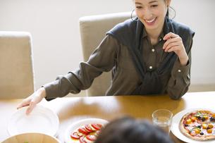 ダイニングテーブルで食事を楽しむ男性と女性の写真素材 [FYI02971795]