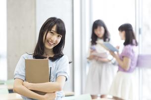 教室で教材を持って微笑む女子学生の写真素材 [FYI02971799]